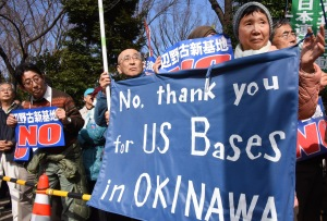 People hold banners as they listen to a speaker during a rally against a new US military base in Okinawa, Japan's nouthernmost prefecture, in front of the National Diet in Tokyo on February 21, 2016. Several hundred people took part in the rally denouncing the central government's plan of constructing a US Marine air base in the remote Henoko part of Okinawa island, to replace the existing Futenma facility located in a heavily populated area. AFP PHOTO / Toru YAMANAKA / AFP / TORU YAMANAKA (Photo credit should read TORU YAMANAKA/AFP/Getty Images)
